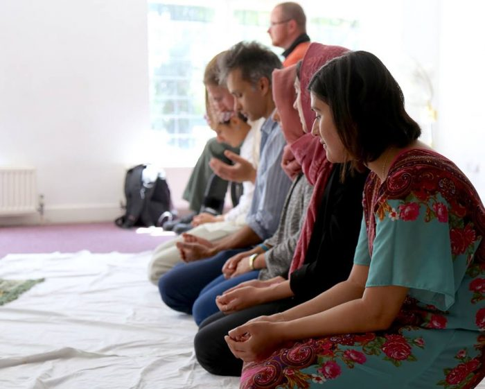 A side view of Muslims praying with people of different genders in one row. The people are of different races, some women are wearing headscarves, some are not. One person is a wheelchair user.