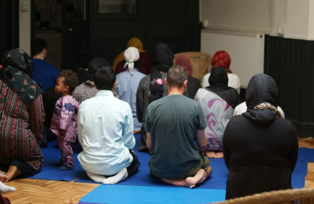 A group of people of all genders sit and pray together