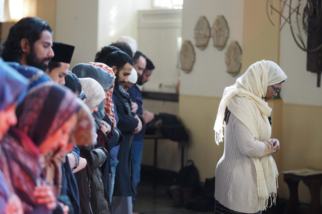 A female imam leads a prayer, with people of all genders praying side by side behind her.