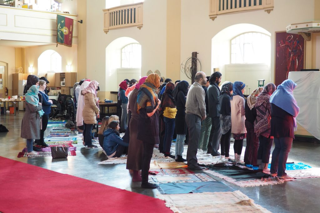 A group of people of all genders pray together in a large hall
