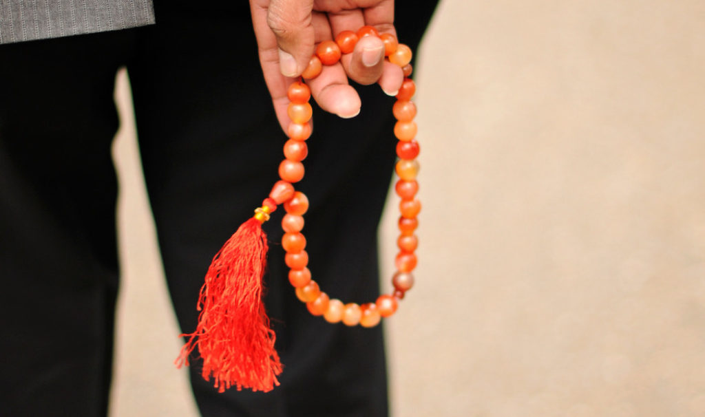 A close up of a brown hand holding an orange rosary.